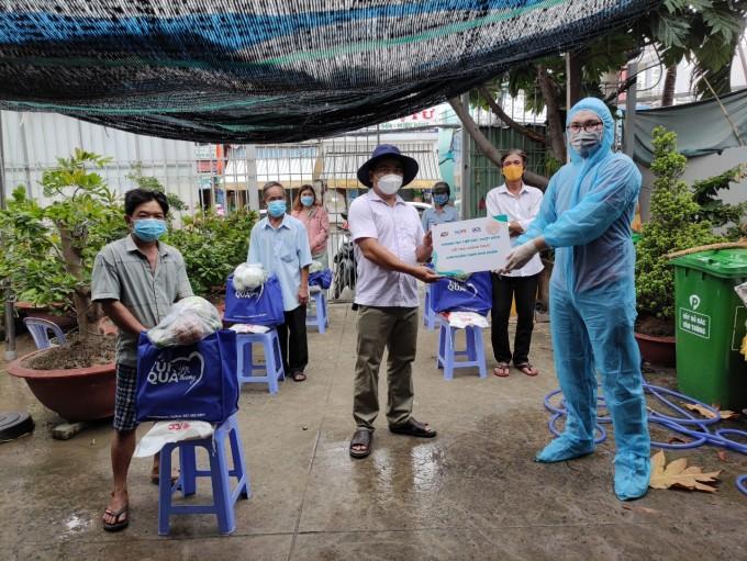 Các hộ khó khăn ở huyện Bình Chánh tiếp nhận quà hỗ trợ từ quỹ Hy vọng. Ảnh: Tuấn Kiệt.