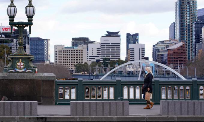 Một người phụ nữ đi trên con phố vắng bóng người vì lệnh phong tỏa ở Melbourne, bang Victoria hôm 16/7. Ảnh: Reuters.