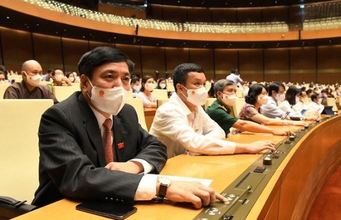 Ông Bùi Văn Cường, Tổng thư ký Quốc hội (bìa trái) bấm nút thông qua Nghị quyết. Ảnh: Giang Huy