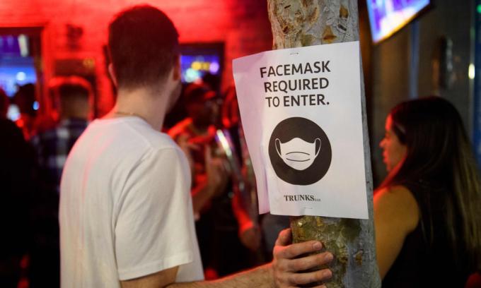 Thông báo yêu cầu đeo khẩu trang được dán phía ngoài một quán bar ở West Hollywood, bang California. Ảnh: AFP.