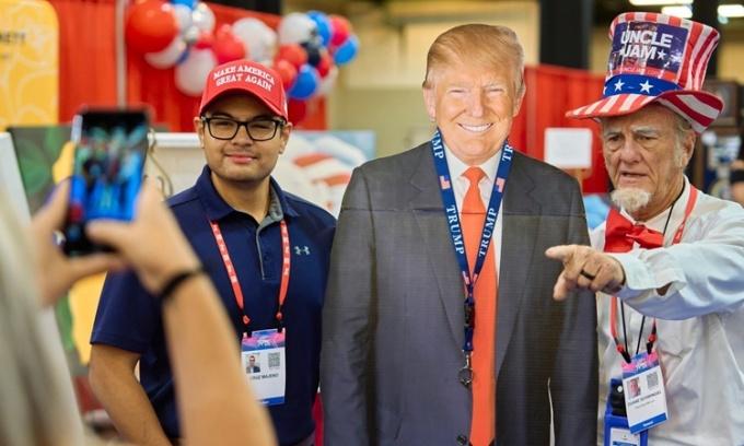 Người ủng hộ chụp ảnh tấm bình cứng in hình ảnh cựu tổng thống Mỹ Donald Trump tại Hội nghị Hành động Chính trị của đảng Bảo thủ ở Dallas. Ảnh: NYTimes.