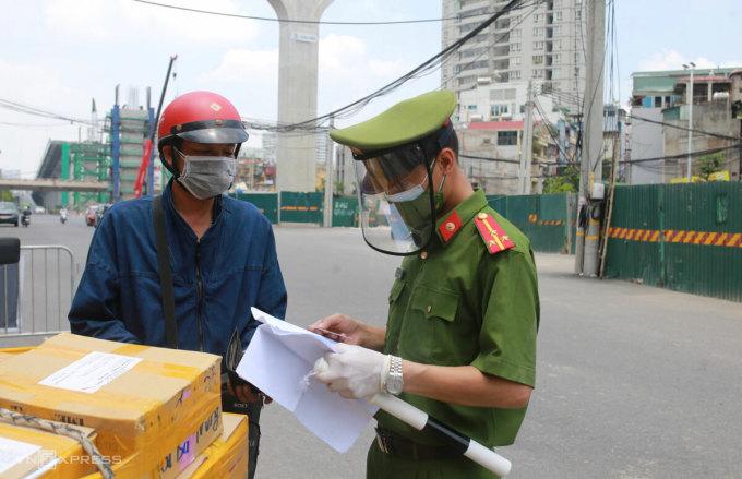 Cảnh sát kiểm tra giấy tờ một người giao hàng trưa 29/7 trên phố Đại La. Ảnh:Tất Định