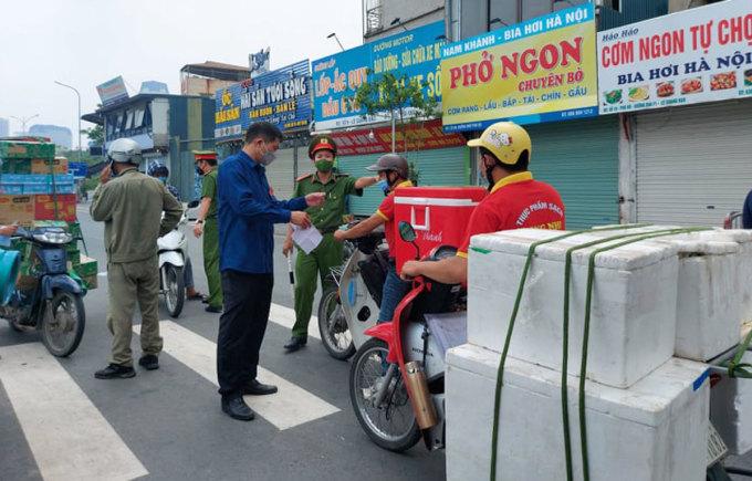 Lực lượng chức năng kiểm tra giấy tờ những người giao hàng, ai không có mã nhận diện luồng xanh của ngành giao thông sẽ phải quay đầu. Ảnh: Duẩn Văn
