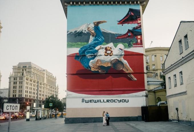 Bức tranh tường cho thấy võ sĩ trong bộ kimono có biểu tượng con gấu lật một đối thủ trong bộ kimono có biểu tượng WADA. Ảnh: NYTimes.