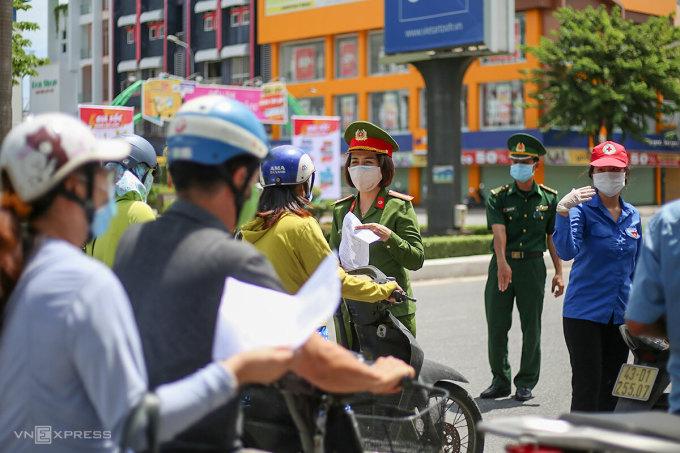 Lực lượng chức năng kiểm tra giấy đi đường của người dân, trưa 3/8. Ảnh: Nguyễn Đông.