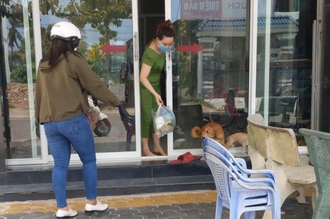 Bạn Nguyễn Thị Hằng giao hàng sau khi đi chợ giúp cho người dân trên đường Hoàng Bích Sơn, phường Phú Thủy. Ảnh: Tư Huynh.