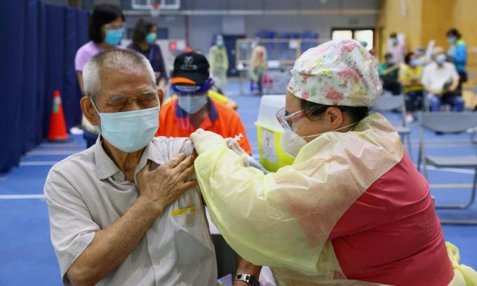 Nhân viên y tế tiêm vaccine Covid-19 cho người dân tại một điểm tiêm chủng ở thành phố Tân Bắc trên đảo Đài Loan hôm 25/6. Ảnh: Reuters.