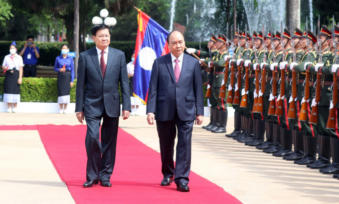 Tổng bí thư, Chủ tịch nước Lào (trái) và Chủ tịch nước Nguyễn Xuân Phúc trong lễ đón tại Vientiane sáng 9/8. Ảnh: BNG.