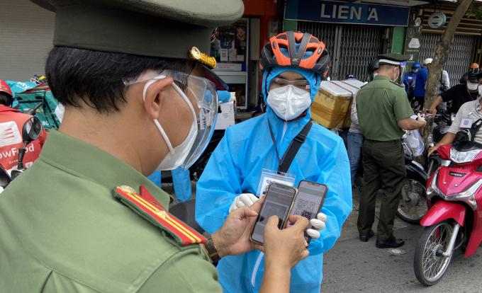 Cảnh sát kiểm tra mã QR của người dân khai báo tại chốt kiểm soát đường Phan Đăng Lưu, quận Bình Thạnh, chiều 14/8. Ảnh: Hạ Giang.