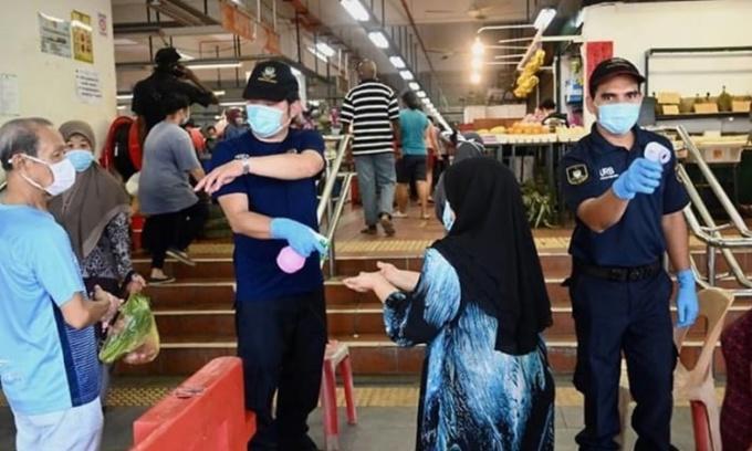 Nhân viên an ninh kiểm tra nhiệt độ và phun sát khuẩn tay cho người vào một khu chợ ở Penang, Malaysia, hồi tháng 5 năm ngoái. Ảnh: AFP.