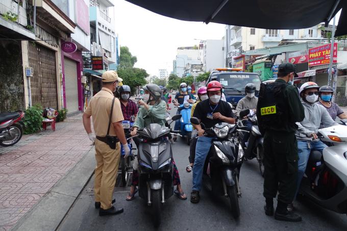 Cảnh sát kiểm tra giấy tờ người dân qua chốt đường Nơ Trang Long, quận Bình Thạnh, chiều 17/8. Ảnh: Hà An