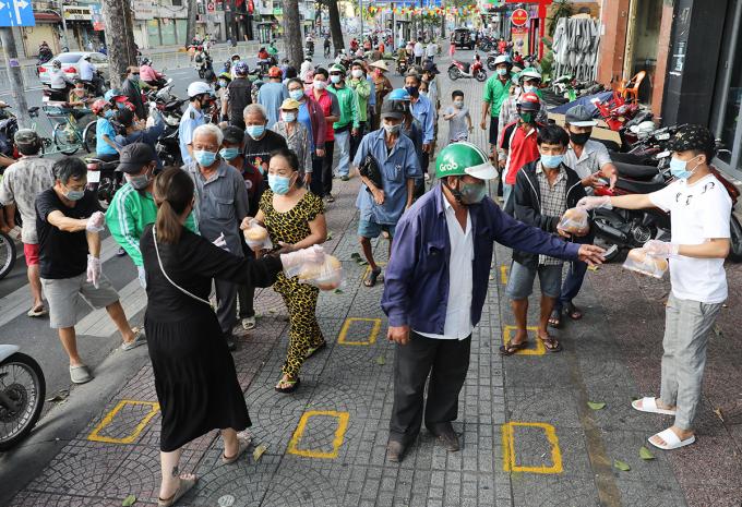 Người dân nhận lương thực tại điểm từ thiện ở quận 1, ngày 18/6. Ảnh: Quỳnh Trần