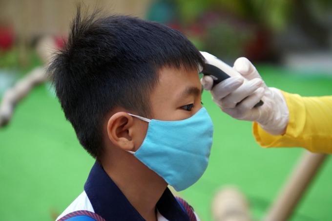 Học sinh trường Tiểu học Nguyễn Bỉnh Khiêm, quận 1 được đo thân nhiệt trước giờ vào lớp học tháng 2. Ảnh: Mạnh Tùng
