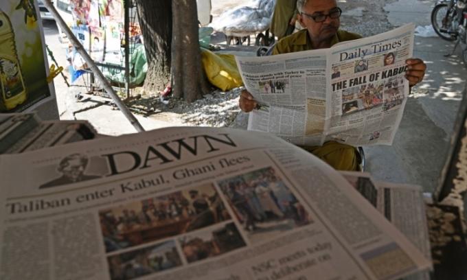Người dân Pakistan đọc các bài báo nói về chiến thắng của Taliban tại Afghanistan ở một sạp báo tại Islamabad hôm 16/8. Ảnh: AFP.