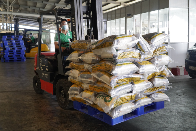 Công nhân Chi nhánh Công ty Cổ phần Tập đoàn Tân Long tại Đồng Tháp bốc dỡ gạo chuẩn bị đưa lên xe tải để đưa đi tiêu thụ. Ảnh: Ngọc Tài