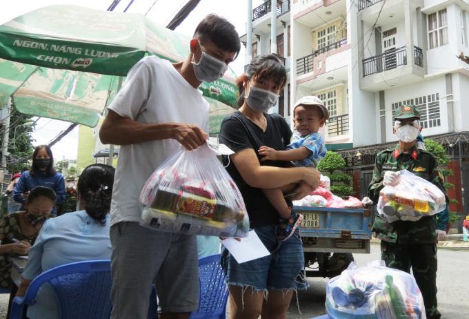 Gia đình chị Huỳnh Hải Vân ở trọ tại 549/36 Lê Văn Thọ, phường 14 (quận Gò Vấp) nhận túi an sinh, tiền hỗ trợ từ chính quyền. Ảnh: Lê Tuyết