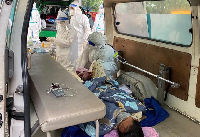 Hai mẹ con sản phụ được xe cấp cứu chở vào bệnh viện sau khi vượt cạn bên đường. Ảnh: Đinh Sự