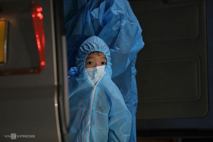 Em bé theo người thân rời khỏi ngõ 328 - 330 Nguyễn Trãi, ổ dịch lớn nhất phường Thanh Xuân Trung, Hà Nội đi cách ly tập trung tại KTX Đại học FPT Hòa Lạc, đêm 1/9. Ảnh: Ngọc Thành