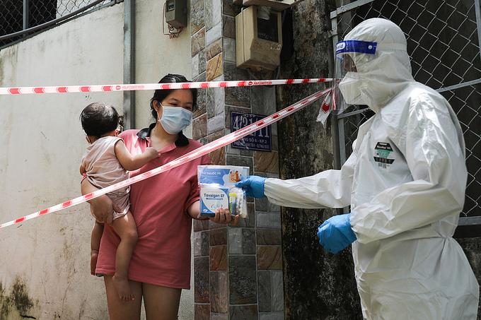 Nhân viên y tế phường Linh Tây, TP Thủ Đức, thăm khám và phát thuốc cho chị Mỹ Duyên, 28 tuổi, một F0 đang điều trị tại nhà, ngày 3/9. Ảnh: Quỳnh Trần.