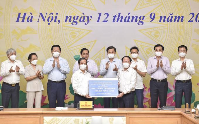 Bộ trưởng GIáo dục và Đào tạo Nguyễn Kim Sơn đại diện ban tổ chức chương trình Sóng và máy tính cho em nhận hỗ trợ từ các đơn vị trong lễ phát động tối 12/9. Ảnh: MOET