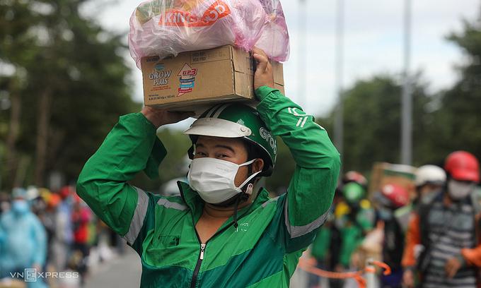 Shipper đứng xếp hàng chờ giao đồ trước bệnh viện dã chiến số 6 (TP Thủ Đức). Ảnh: Thành Nguyễn