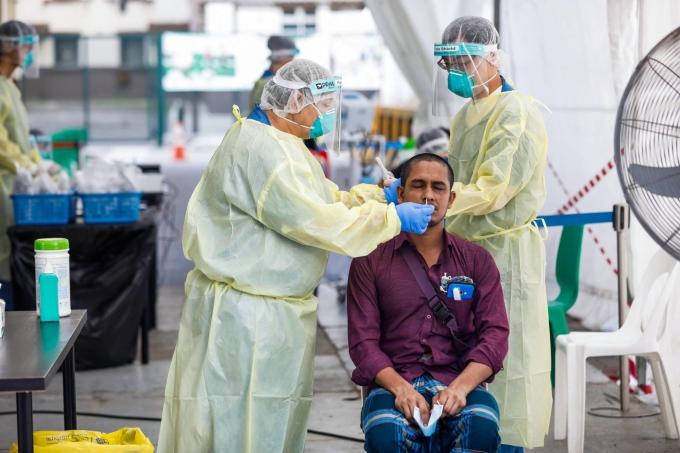 Nhân viên y tế Singapore lấy mẫu cho một lao động nhập cư hôm 15/5. Ảnh: AFP.