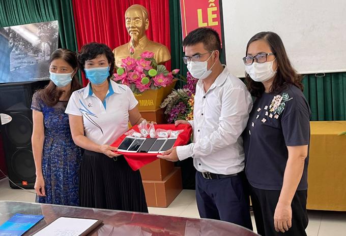 Cô Vương Thị Quyên (thứ hai từ phải sang), Hiệu trưởng trường Tiểu học Phù Đổng, nhận điện thoại từ thầy Dũng (áo trắng) hôm 4/9. Ảnh: Nhân vật cung cấp