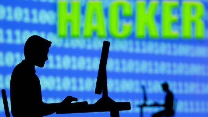 Minh họa người làm việc trước máy tính trên nền mã nhị phân và từ tin tặc. Đồ họa: Reuters.