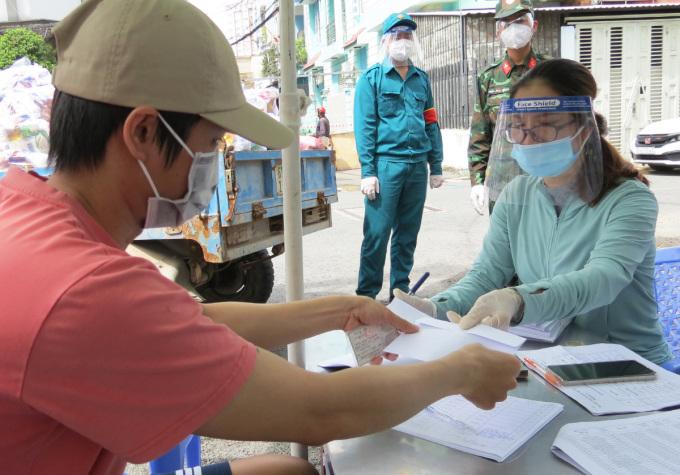 Người dân (trái) phường 14, quận Gò Vấp nhận hỗ trợ đợt 2. Ảnh: Lê Tuyết