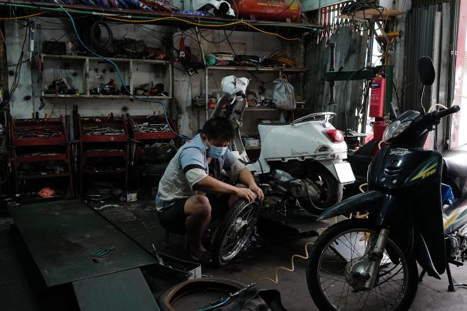 Thợ sửa xe máy trên phố Đội Cấn, quận Ba Đình, Hà Nội, đón khách hàng đầu tiên sau gần 2 tháng đóng cửa giãn cách, ngày 16/9. Ảnh: Ngọc Thành