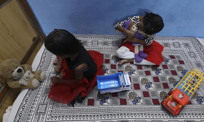 Hai chị em song sinh tại Ấn Độ mất bố mẹ vì Covid-19 được chuyển đến sống cùng họ hàng tại tỉnh Bhopal vào tháng 6. Ảnh: AFP.