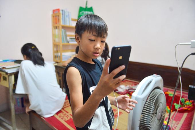 Cậu con trai lớp 3 của chị Hồng chỉ có thể tranh thủ học online khi các chị nghỉ giải lao. Ảnh: Phạm Chiểu