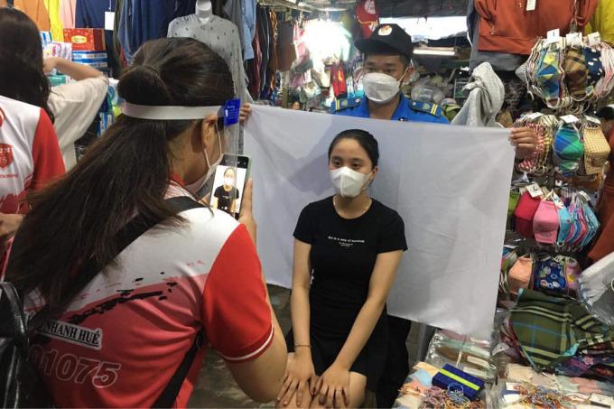 Lực lượng tình nguyện chụp ảnh làm thẻ kiểm soát dịch bệnh cho tiểu thương chợ Đông Ba. Ảnh: Vạn An