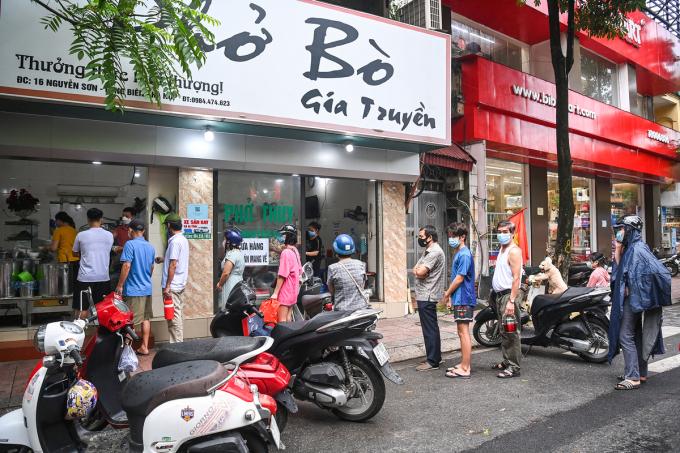 Trưa 16/9, khách xếp hàng trước quán phở trên phố Nguyễn Sơn (quận Long Biên) để mua mang về sau khi thành phố nới lỏng giãn cách tại 19 quận, huyện vùng xanh. Ảnh: Giang Huy.