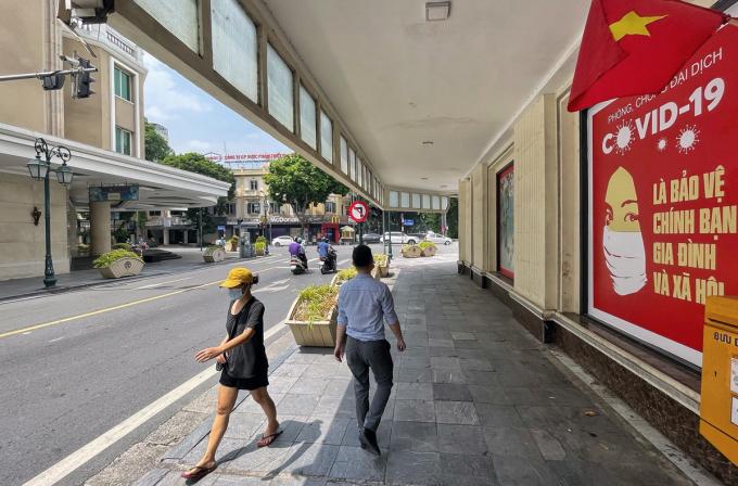 Người dân đi qua tấm pano tuyên truyền phòng dịch Covid-19 trên phố Tràng Tiền (Hoàn Kiếm), sáng 20/9. Ảnh:Giang Huy