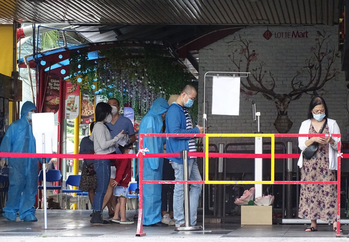 Khách hàng được kiểm tra các biện pháp phòng dịch trước khi vào siêu thị Lotte Mart, quận 7. Ảnh: Hà An