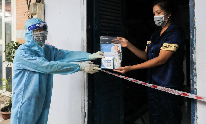 Nhân viên y tế phường 3, quận 8, TP HCM đến thăm khám, đo sPO2, tặng thuốc cho người mắc Covid-19 đang điều trị tại nhà, ngày 29/8. Ảnh: Quỳnh Trần
