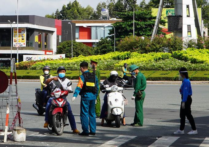 Kiểm tra giấy đi đường tại chốt kiểm soát đường Nguyễn Bỉnh Khiêm, quận 1, hôm 23/8. Ảnh: Gia Minh