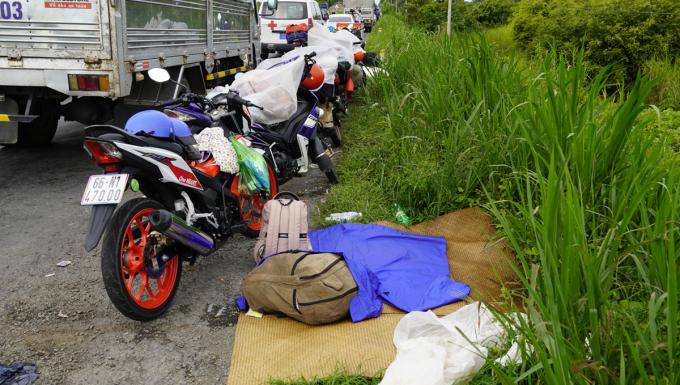 Bạt, đệm, hành lý cùng xe máy của nhóm người từ Long An về Đồng Tháp đang bị kẹt tại chốt thị trấn Mỹ An, Đồng Tháp trưa nay. Ảnh: Hoàng Nam