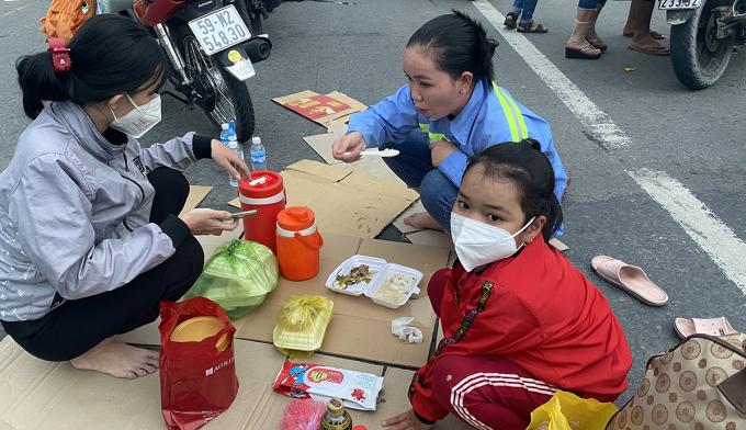 Người dân ăn cơm ngay trên đường trong lúc chờ đợi qua chốt kiểm soát. Ảnh: Cửu Long