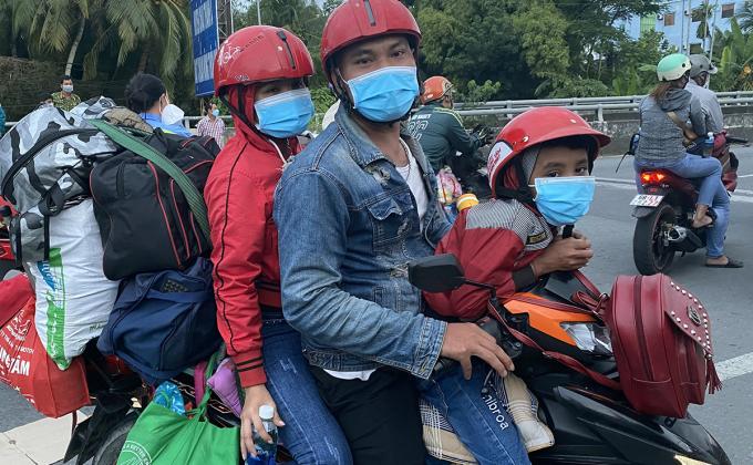 Anh Sơn Chanh So cùng vợ con chờ đợi để được phép đi qua địa phận tỉnh Hậu Giang để về Sóc Trăng, chiều 25/9. Ảnh: Cửu Long