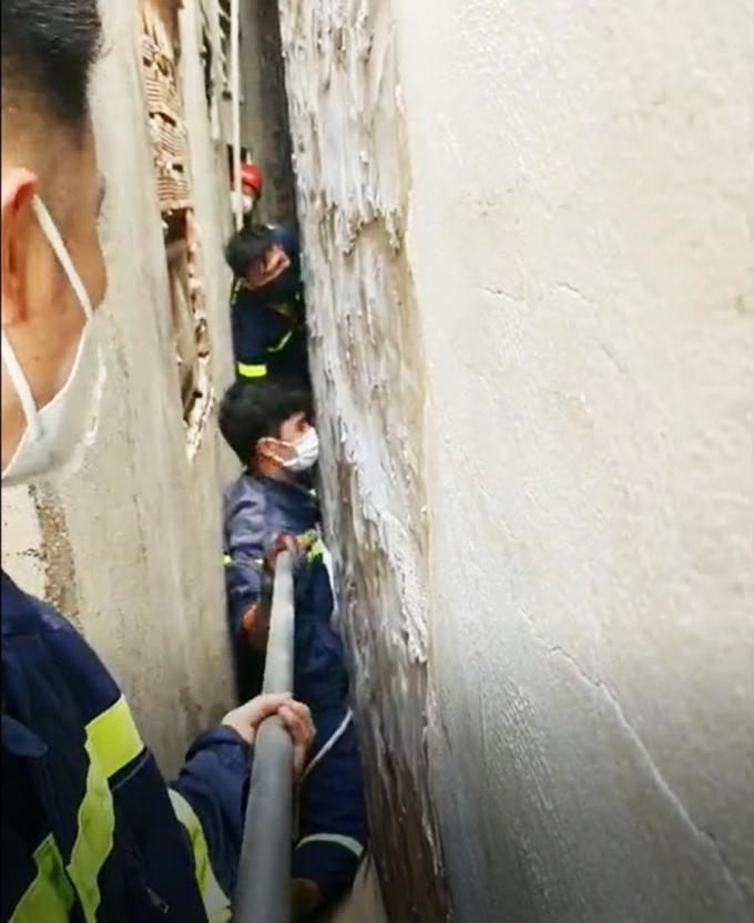 Lính cứu hỏa chuyền thanh sắt cho đồng đội để nhấc, đưa nạn nhân ra ngoài. Ảnh: Công an cung cấp