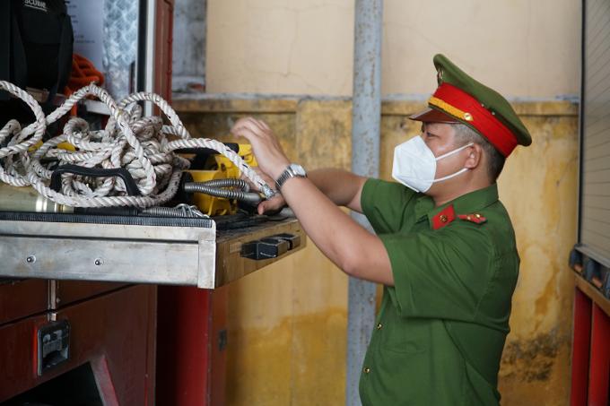 Đại úy Đỗ Anh Linh kiểm tra trang thiết bị trên xe cứu hỏa, sáng 27/9. Ảnh: Trường Hà