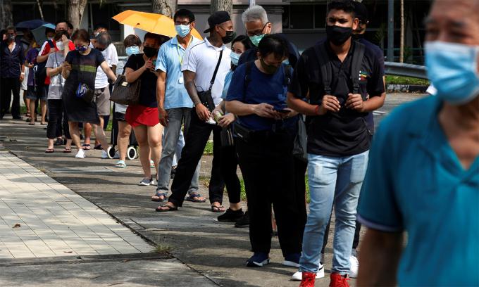 Người dân Singapore xếp hàng chờ bên ngoài một trung tâm xét nghiệm nhanh nCoV ngày 21/9. Ảnh: Reuters.