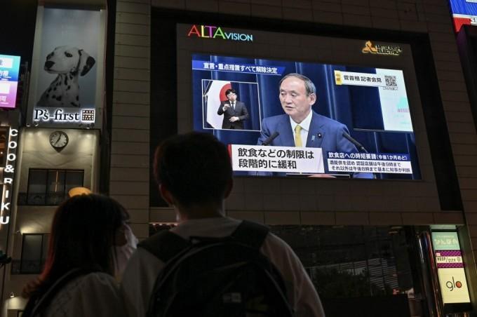 Người dân Tokyo theo dõi Thủ tướng Yoshihide Suga tuyên bố dỡ tình trạng khẩn cấp qua truyền hình trực tiếp hôm 28/9. Ảnh: AFP