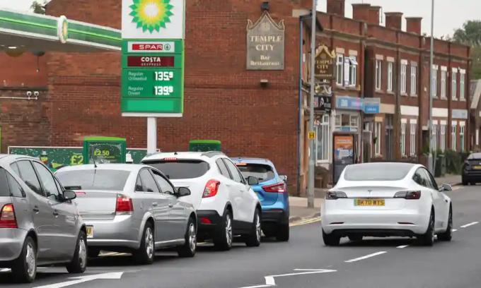 Một chiếc xe điện Tesla chạy ngang qua hàng ôtô xếp hàng vào một trạm xăng dầu ở Peterborough, Anh. Ảnh: Paul Marriott/Rex/Shutterstock