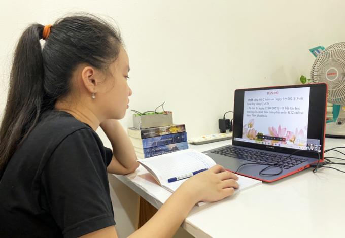 Vũ Hà Bảo Hân, học sinh lớp 6 trường THCS Nguyễn Du (quận 1) nghe cô giáo chủ nhiệm dặn dò nội quy học trực tuyến, sáng 1/9. Ảnh: Phụ huynh cung cấp