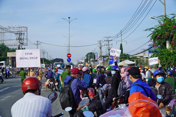 Người dân được bố trí theo từng nhóm, cầm bảng theo địa phương, chờ sắp xếp xe đón về quê, sáng 1/10. Ảnh: Gia Minh