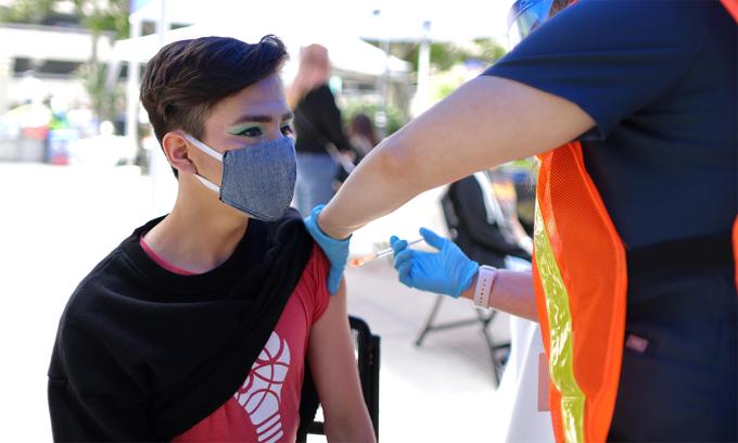 Nhân viên y tế Mỹ tiêm vaccine Covid-19 cho một thiếu niên 16 tuổi tại Pasadena, California ngày 14/5. Ảnh: Reuters.
