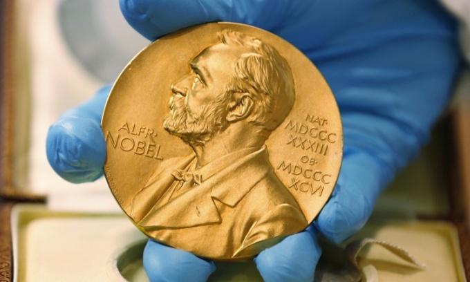 Một nhân viên Thư viện Quốc gia Colombia cầm trên tay huy chương Nobel được trao cho tiểu thuyết gia quá cố Gabriel Garcia Marquez ngày 17/4/2015. Ảnh: AP.